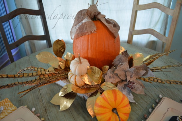 pumpkin centerpiece with gold leaves and feathers